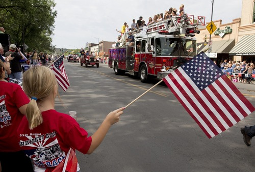 Spectators stand as a Prescott Fire Department engine, carrying family members of the 19 fallen Granite Mountain Hotshot firefighters, slowly rolls down Montezuma Street during the Prescott Frontier Days Rodeo Parade, Saturday, July 6, 2013 in Prescott, Ariz. The procession of fire trucks started the parade to honor the Hotshots who were killed battling a blaze near Yarnell, Ariz. last week. (AP Photo/Julie Jacobson)