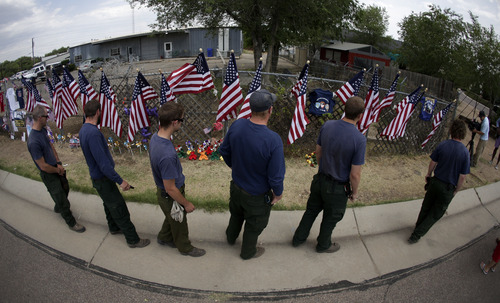 FILE - In this July 4, 2013 file photo, members of the Centennial, IA Fire Crew, pay their respects at a memorial outside the Granite Mountain Interagency Hotshot Crew fire station in Prescott, Ariz. Ninteen firefighters from Granite Mountain Interagency Hotshot Crew were killed battling a wildfire near Yarnell, Ariz., Sunday. The elite crew of firefighters were overtaken by the out-of-control blaze as they tried to protect themselves from the flames under fire-resistant shields. (AP Photo/Chris Carlson, File)