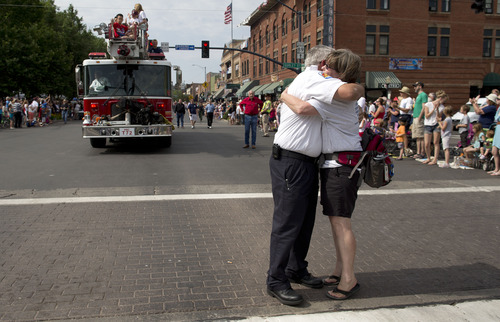 Prescott Fire Marshall Don Devendorf, left, stops to hug long-time friend Laura Halter while walking in the Prescott Frontier Days Rodeo Parade, Saturday, July 6, 2013 in Prescott, Ariz. Devendorf walked ahead of a Prescott Fire Department engine carrying family members of the 19 Granite Mountain Hotshot firefighters who were killed last week fighting a fire near Yarnell, Ariz. (AP Photo/Julie Jacobson)