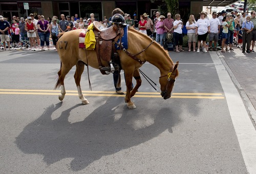 A riderless horse carrying a firefighter's helmet, and boots facing backwards in the stirrups, walks down Cortez Street during the Prescott Frontier Days Rodeo Parade, Saturday, July 6, 2013 in Prescott, Ariz. The riderless horse represented the fallen 19 Granite Mountain Hotshot firefighters who were killed battling a blaze last week near Yarnell, Ariz. (AP Photo/Julie Jacobson)
