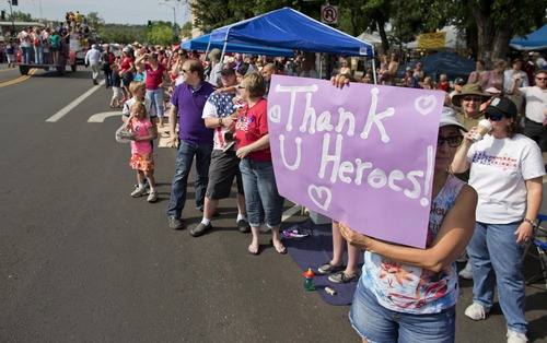 Michele Simmons holds up a sign of gratitude as Prescott Fire Department engines roll by carrying family members of the 19 fallen Granite Mountain Hotshot firefighters at the start of the Prescott Frontier Days Rodeo Parade, Saturday, July 6, 2013 in Prescott, Ariz.  The procession of fire trucks started the parade to honor the Hotshots who were killed battling a blaze near Yarnell, Ariz. last week. (AP Photo/Julie Jacobson)