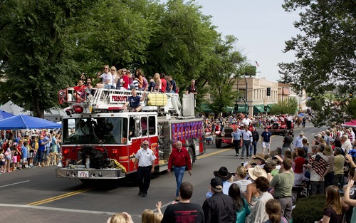 Carrying family members of the 19 fallen Granite Mountain Hotshot firefighters, a Prescott Fire Department fire engine makes its way down Cortez Street during the Prescott Frontier Days Rodeo Parade  Saturday, July 6, 2013 in Prescott, Ariz. Nineteen Hotshot firefighters were killed last week by an out-of-control blaze near Yarnell, Ariz.  (AP Photo/Julie Jacobson)