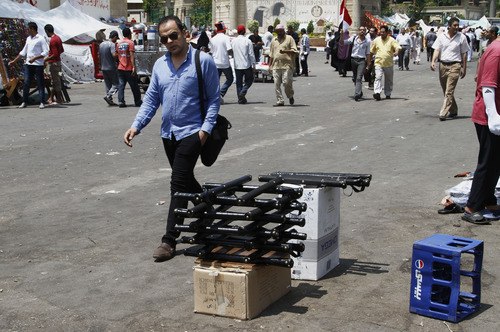 A man walks by a stand selling billy clubs used by supporters of the Muslim Brotherhood near their sit-in in Nasser City, suburb of Cairo, Egypt , Sunday, July 7, 2013. Egypt's new president moved to assert his authority and regain control of the streets Saturday even as his Islamist opponents declared his powers illegitimate and issued blood oaths to reinstate Mohammed Morsi, whose ouster by the military has led to dueling protests and deadly street battles between rival sides. (AP Photo/Paul Schemm)