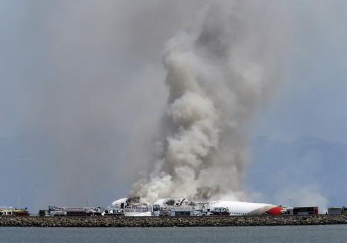 Smokes rises from Asiana Flight 214 after it crashed at San Francisco International Airport in San Francisco, Saturday, July 6, 2013. (AP Photo/Bay Area News Group, John Green)