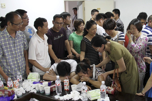 Parents of Wang Linjia, center, are comforted by parents of some other students who were on the Asiana Airlines Flight 214 when it crashed at San Francisco International Airport, while they gather and wait for news of their children at Jiangshan Middle School in Jiangshan city, in eastern China's Zhejiang province, Sunday July 7, 2013. Chinese state media have identified the two people who died in the plane crash at San Francisco International Airport on Saturday as Ye Mengyuan and Wang Linjia, 16-year-old students at Jiangshan Middle School in China's eastern Zhejiang province. (AP Photo)  CHINA OUT