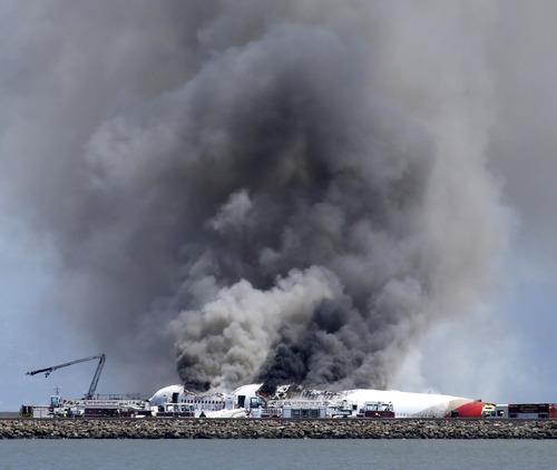 Fire crews work the crash site of Asiana Flight 214 at San Francisco International Airport in San Francisco, Saturday, July 6, 2013. (AP Photo/Bay Area News Group, John Green)