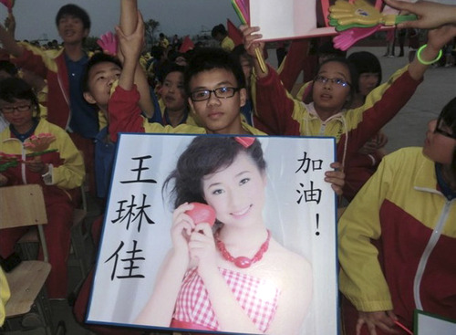 In this undated photo made available Monday, July 8, 2013, a supporter of Wang Linjia, holds up a photo of her with her name during a talent show at a school in Jiangshan city in eastern China's Zhejiang province. Chinese state media and Asiana Airlines have identified the two victims of the Asiana Airlines crash at San Francisco International Airport girls as Ye Mengyuan and Wang Linjia, students in Zhejiang, an affluent coastal province in eastern China.  (AP Photo) CHINA OUT