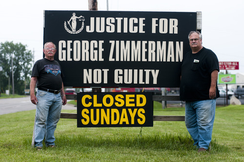 Darwin Groves, left, and Donald Sampson, pose next to a sign that calls for George Zimmerman's innocence, Monday, July 8, 2013, outside of their business in Flint, Mich. George Zimmerman is currently being tried in the 2012 murder case of 17-year-old Trayvon Martin in Sanford, Fla. (AP Photo/The Flint Journal, Jake May) LOCAL TV OUT; LOCAL INTERNET OUT