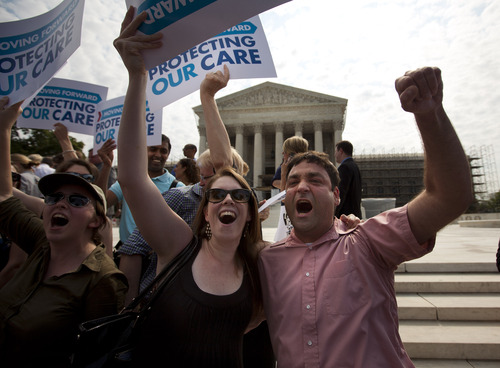 FILE – In this June 28, 2012, file photo Claire McAndrew, left, and Donny Kirsch, both of Washington, celebrate outside the Supreme Court in Washington after the high court upheld President Barack Obama's health care overhaul. Three months before uninsured people can start shopping for coverage, some big unknowns loom amid the surprise announcement last week, July 2013, that the White House is delaying a requirement that many employers offer coverage, has raised questions about other major parts of the biggest expansion of society's safety net since Medicare nearly 50 years ago. People will judge Obama's law on three main points: premiums, choice and the overall consumer experience. (AP Photo/Evan Vucci, File)