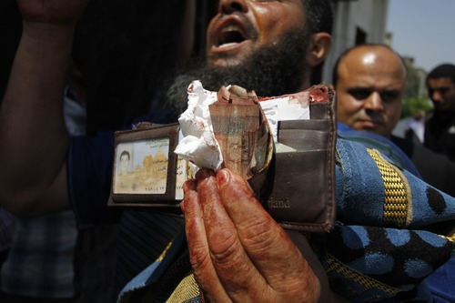 A man displays a bloodied wallet belonging to a supporter of ousted President Mohamed Morsi's outside a local hospital in Cairo. Egypt, Monday, July 8, 2013. Egyptian soldiers and police opened fire on supporters of the ousted president early Monday in violence that left dozens of people killed, including one officer, outside a military building in Cairo where demonstrators had been holding a sit-in, government officials and witnesses said.  .(AP Photo/Nasser Shiyoukhi)