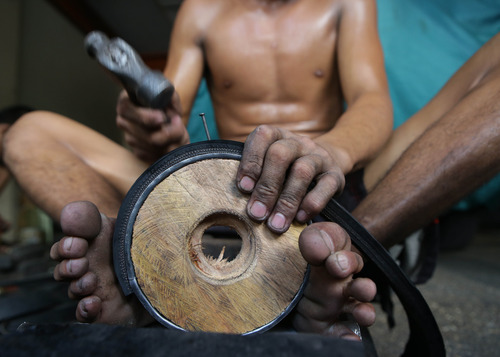 A Filipino man uses his feet to hold a wooden wheel to fasten strips of used rubber tires at a shop selling pushcart wheels made from used materials in Manila, Philippines on Monday July 8, 2013. The wheel sets made from used wheel bearings, old rubber tires, used tin cans and steel rods are sold from P500 to P1,600 (US $11 to $37) per set of three. (AP Photo/Aaron Favila)