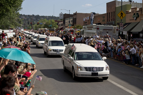 Hundreds of people line Montezuma Street Sunday, July 7, 2013 in downtown Prescott, Ariz. to pay respects as 19 hearses slowly roll by carrying the 19 Granite Mountain Hotshot firefighters killed a week ago by an out-of-control blaze near Yarnell, Ariz. The nearly five-hour-long procession began near the state Capitol in Phoenix, went through the town where the Granite Mountain Hotshots were killed and ended in the mountain community of Prescott, where they lived and will be laid to rest this week. (AP Photo/Julie Jacobson)