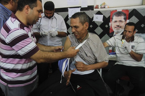 An injured is helped in a makeshift hospital after Egyptian soldiers and police opened fire on supporters of the ousted President Mohammed Morsi early Monday in Cairo,  Egypt, Monday, July 8 , 2013. The violence left dozens  people killed outside the Republican Guard military building in Cairo where demonstrators had been holding a sit-in, government officials and witnesses said. (AP Photo/ Ahmed Gomaa )
