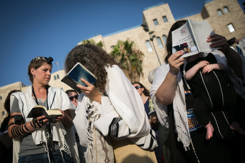 """Israeli Jewish women of the Women of the Wall organization pray while wearing  prayer shawls just outside the Western Wall, the holiest site where Jews can pray in Jerusalem's Old City, Monday, July 8, 2013. Police denied Women of the Wall and their supporters  entry to the women's prayer section, citing security concerns. The group, known as """"Women of the Wall,"""" convenes monthly prayer services at the Western Wall, wearing prayer shawls and performing rituals that Ultra-Orthodox Jews believe only men are allowed to do. (AP Photo/Michal Fattal) ***ISRAEL OUT***"""