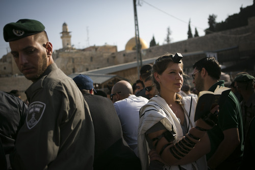 """An Israeli Jewish woman of the Women of the Wall organization prays while wearing a prayer shawl outside the Western Wall, the holiest site where Jews can pray in Jerusalem's old city, Monday, July 8, 2013. Police denied Women of the Wall and their supporters entry to the women's prayer section, citing security concerns. The group, known as """"Women of the Wall,"""" convenes monthly prayer services at the Western Wall, wearing prayer shawls and performing rituals that ultra-Orthodox Jews believe only men are allowed to do. (AP Photo/Michal Fattal) ***ISRAEL OUT***"""