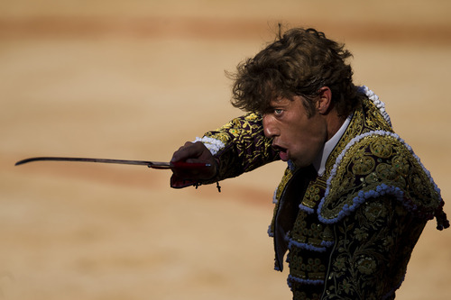 """Spanish bullfighter Manuel Escribano aims his sword before killing a Dolores Aguirre fighting bull during a bullfight of the San Fermin festival, in Pamplona, Spain, Monday, July 8, 2013. Revelers from around the world arrive to Pamplona every year to take part on some of the eight days of the running of the bulls glorified by Ernest Hemingway's 1926 novel """"The Sun Also Rises."""" (AP Photo/Daniel Ochoa de Olza)"""