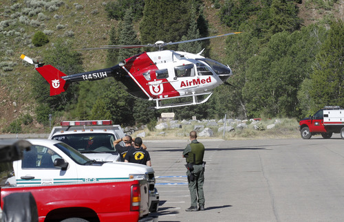 Al Hartmann  |  The Salt Lake Tribune AirMed helicopter touches down at Tibble Fork Reservoir parking lot in American Fork Canyon Monday July 8 to pick up search and rescue personnel to help in the recovery of two injured men whose helicopter crashed and rolled after hitting a hill high up in the mountains near the Utah-Salt Lake County line.  They were able to extricate themselves from the wreck and use a cell phone to call for help about 8:30 a.m.