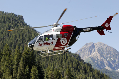 Al Hartmann  |  The Salt Lake Tribune AirMed helicopter heads back for the high country with search and rescue members aboard in American Fork Canyon Monday July 8 to to help in the recovery of two injured men whose helicopter crashed and rolled after hitting a hill in the mountains near the Utah-Salt Lake County line. They were able to extricate themselves from the wreck and use a cellphone to call for help about 8:30 a.m.