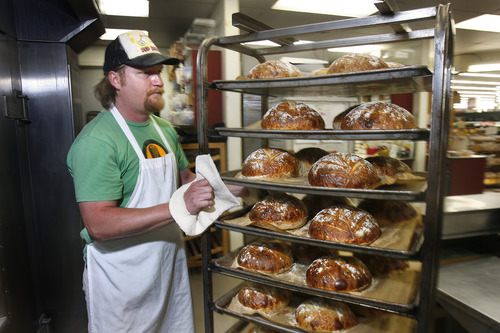 """Scott Sommerdorf     The Salt Lake Tribune Brent Whitford of Red Bicycle Breadworks wheels fresh """"boule"""" loaves from the oven in Park City, Sunday, July 7, 2013. For some businesses the Park Silly Sunday Market is a chance to try out their products and see if the public likes it. The Park Silly Sunday Market is celebrating its fifth season and 100th market on Historic Main Street."""