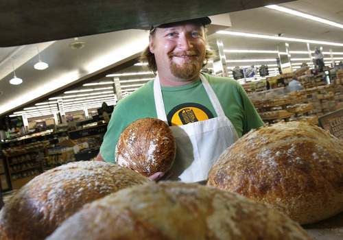 """Scott Sommerdorf     The Salt Lake Tribune Brent Whitford of Red Bicycle Breadworks poses near fresh """"boule"""" loaves from the oven in Park City, Sunday, July 7, 2013. For some businesses the Park Silly Sunday Market is a chance to try out their products and see if the public likes it. The Park Silly Sunday Market is celebrating its fifth season and 100th market on Historic Main Street."""