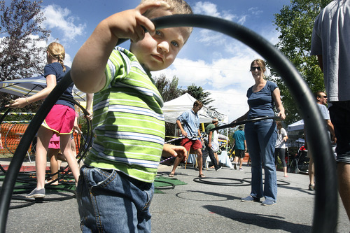 Scott Sommerdorf  |  The Salt Lake Tribune Two-year-old Isaac Jenkins tries out the hula hoops at the Park Silly Market, Sunday, July 7, 2013. For some businesses the Park Silly Sunday Market is a chance to try out their products and see if the public likes it. The Park Silly Sunday Market is celebrating its fifth season and 100th market on Historic Main Street.