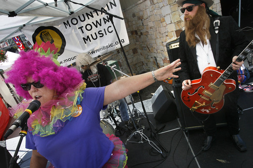 """Scott Sommerdorf     The Salt Lake Tribune Kim Page introduces """"Tres Hombres"""" -- a ZZ Top cover band from Taylorsville -- at the Park Silly Market, Sunday July 7, 2013. For some businesses the Park Silly Sunday Market is a chance to try out their products and see if the public likes it. The Park Silly Sunday Market is celebrating its fifth season and 100th market on Historic Main Street."""