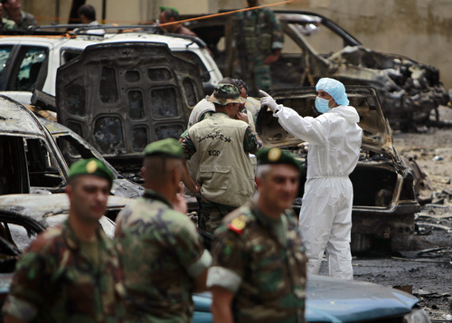 Forensic experts and security forces stand at the scene of a bombing in the Beir el-Abed, a southern suburb of Beirut, Lebanon, Tuesday, July 9, 2013. A large explosion rocked a stronghold of the Shiite militant Hezbollah group south of the Lebanese capital Tuesday, setting several cars on fire, sending a thick plume of black smoke billowing into the sky and wounding more than a dozen people, security officials said. (AP Photo/Bilal Hussein)