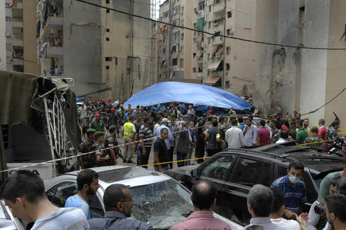 Security forces and civilians stand at the scene of a bombing in the Beir el-Abed, a southern suburb of Beirut, Lebanon, Tuesday, July 9, 2013. A large explosion rocked a stronghold of the Shiite militant Hezbollah group south of the Lebanese capital Tuesday, setting several cars on fire, sending a thick plume of black smoke billowing into the sky and wounding more than a dozen people, security officials said.(AP Photo/Ahmed Omar)