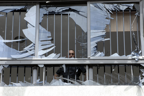 Ahmed Omar  |  The Associated Press A man peers through a shattered window at the scene of a bombing in the Beir el-Abed, a southern suburb of Beirut, Lebanon, on Tuesday. A large explosion rocked a stronghold of the Shiite militant Hezbollah group south of the Lebanese capital Tuesday, setting several cars on fire, sending a thick plume of black smoke billowing into the sky and wounding more than a dozen people, security officials said.