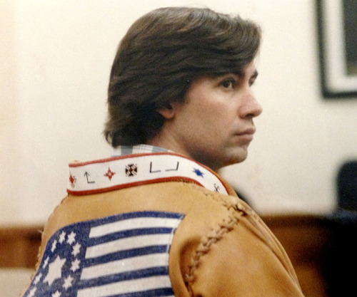 "Tribune file photo  Addam Swapp at a 1988 court hearing wearing the buckskin coat made by his wives. The collar was adorned with Indian and geometric symbols. The flag was designed by John Singer, who called it the ""Banner of the Kingdom of God."""