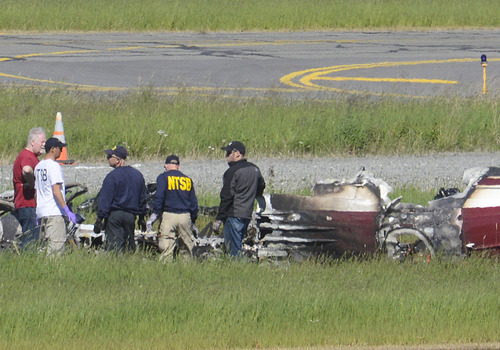 National Transportation and Safety Board go-team members examine the remains of an aircraft wreck on Monday, July 8, 2013 in Soldotna, Alaska.  The de Havilland DHC3 Otter crashed and burned Sunday, July 7, 2013 at the airport in Soldotna, about 75 miles southwest of Anchorage on the Kenai Peninsula. The plane had just taken off and apparently was en route to a fishing lodge, according to National Transportation Safety Board investigator Clint Johnson. All ten people aboard were killed.   (AP Photo/Peninsula Clarion, Rashah McChesney)