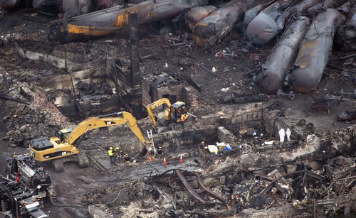 Workers comb through the debris Tuesday, July 9, 2013 in Lac-Magantic, Quebec.  The fiery oil train derailment early Saturday caused explosions and fires that devasted the town.  (AP Photo/The Canadian Press, Paul Chiasson)
