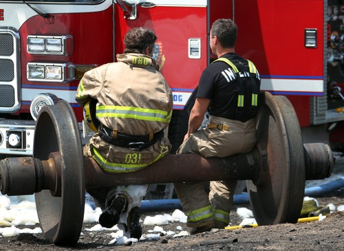 In a Sunday, July 7, 2013 photo, firefighters take a break on a set of train wheels in Lac-Megantic, Quebec, in a Surete du Quebec handout photo made available Tuesday, July 9, 2013. Thirteen people are confirmed dead and forty more are listed as missing after a train derailed ignited tanker cars carrying crude oil. (AP Photo/Surete du Quebec via The Canadian Press)
