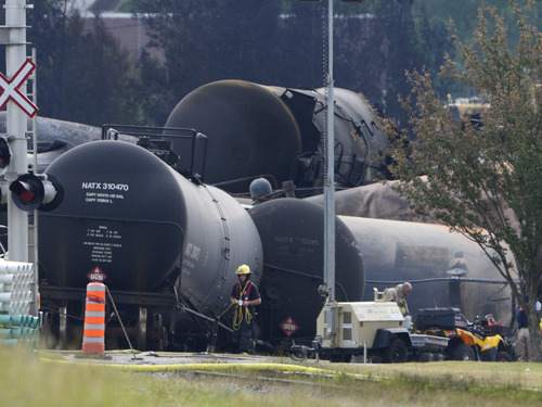 Cleanup continues at the scene of the Lac-Megantic, Quebec, runaway oil train derailment and explosion, Tuesday, July 9, 2013. Investigators looking for the cause of the fiery oil train derailment are zeroing in on whether an earlier blaze on the same train may have set off a chain of events that led to the explosions that killed at least 13 people. (AP Photo/The Canadian Press, Ryan Remiorz)