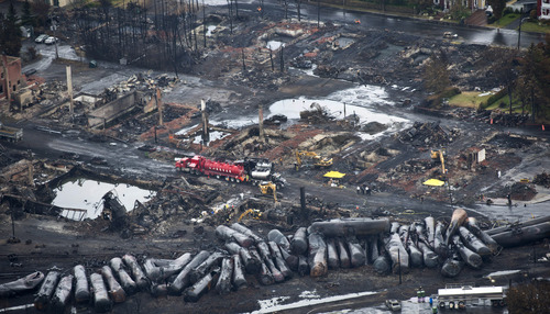 Workers comb through debris Tuesday, July 9, 2013, after a train derailed Saturday causing explosions of railway cars carrying crude oil in Lac-Megantic, Quebec. (AP Photo/The Canadian Press, Paul Chiasson)