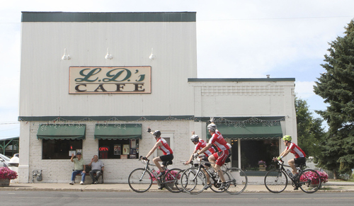 Keith Johnson | The Salt Lake Tribune  Royd VanOrden (left) and Lee Thompson wave to passing cyclists outside L.D.'s Cafe in Richmond, Utah during the MS 150 bike ride through Cache Valley, Utah June 29, 2013.