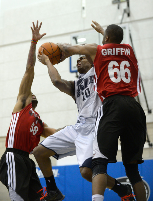 Utah Jazz guard Alec Burks (10) goes up for a shot between Miami Heat guard D.J. Kennedy, left, and Eric Griffin (66) during the first half of an NBA Orlando Pro Summer League game in Orlando, Fla., Sunday, July 7, 2013. (Special to the Tribune/Phelan M. Ebenhack)