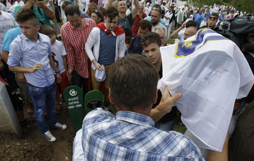 Bosnian men carry the small coffin of Hava Muhic's baby during a mass funeral for Srebrenica victims in memorial center Potocari, near Srebrenica, 160 kms east of Sarajevo, Bosnia, on Thursday, July 11, 2013. Hava Muhic believes she should be baking a cake, with her husband and calling friends and family for the party. Instead, Muhic stood above the smallest pit in the cemetery, near her husband's grave which was dug for her baby girl who died here 18 years ago on the day of the worst massacre Europe has seen since World War II. Muhic's baby is among 409 newly identified victims of the Srebrenica massacre buried on Thursday in an annual mass funeral at the Potocari Memorial Center on the July 11 anniversary. This year's commemorations bring the total of identified victims to 6,066. Another 2,306 remain missing.(AP Photo/Amel Emric)