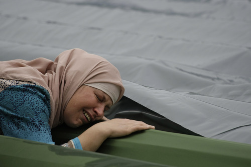 A Bosnian woman cries near the coffin of her relative during a funeral ceremony at the memorial center in Potocari, near Srebrenica, 160 kms east of Sarajevo, Bosnia, Thursday, July 11, 2013. People from around Bosnia and abroad have begun arriving in Srebrenica Thursday to commemorate 18th anniversary of the 1995 massacre and rebury recently identified victims exhumed from mass graves. The victims' bodies are still being exhumed from mass graves in the area, where Serbs had dumped them in an attempt to cover up the crime. Identified victims are buried each year on the massacre's anniversary at a memorial cemetery near Srebrenica. (AP Photo/Amel Emric)