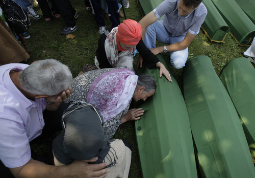 A Bosnian family comfort a woman who cries over the coffin of her son during a funeral ceremony at the memorial center in Potocari, near Srebrenica, 160 kms east of Sarajevo, Bosnia, Thursday, July 11, 2013. People from around Bosnia and abroad have begun arriving in Srebrenica Thursday to commemorate 18th anniversary of the 1995 massacre and rebury recently identified victims exhumed from mass graves. The victims' bodies are still being exhumed from mass graves in the area, where Serbs had dumped them in an attempt to cover up the crime. Identified victims are buried each year on the massacre's anniversary at a memorial cemetery near Srebrenica. (AP Photo/Amel Emric)