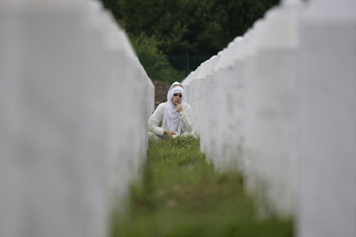 Bosnian woman Zumreta Ahmetasevic prays amidst gravestones during a funeral ceremony at the memorial center in Potocari, near Srebrenica, 160 kms east of Sarajevo, Bosnia, Thursday, July 11, 2013. People from around Bosnia and abroad have begun arriving in Srebrenica Thursday to commemorate 18th anniversary of the 1995 massacre and rebury recently identified victims exhumed from mass graves. The victims' bodies are still being exhumed from mass graves in the area, where Serbs had dumped them in an attempt to cover up the crime. Identified victims are buried each year on the massacre's anniversary at a memorial cemetery near Srebrenica. (AP Photo/Amel Emric)