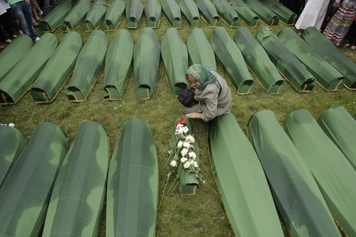 A Bosnian woman says prayers next to the coffin of a child during a funeral ceremony at the memorial center in Potocari, near Srebrenica, 160 kms east of Sarajevo, Bosnia, Thursday, July 11, 2013. People from around Bosnia and abroad have begun arriving in Srebrenica Thursday to commemorate 18th anniversary of the 1995 massacre and rebury recently identified victims exhumed from mass graves. The victims' bodies are still being exhumed from mass graves in the area, where Serbs had dumped them in an attempt to cover up the crime. Identified victims are buried each year on the massacre's anniversary at a memorial cemetery near Srebrenica. (AP Photo/Amel Emric)