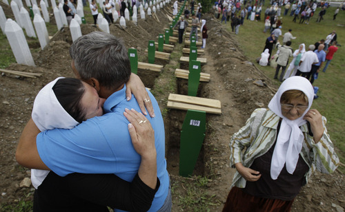 A Bosnian woman is comforted by family members during a funeral ceremony at the memorial center in Potocari, near Srebrenica, 160 kms east of Sarajevo, Bosnia, Thursday, July 11, 2013. People from around Bosnia and abroad have begun arriving in Srebrenica Thursday to commemorate 18th anniversary of the 1995 massacre and rebury recently identified victims exhumed from mass graves. The victims' bodies are still being exhumed from mass graves in the area, where Serbs had dumped them in an attempt to cover up the crime. Identified victims are buried each year on the massacre's anniversary at a memorial cemetery near Srebrenica. (AP Photo/Amel Emric)