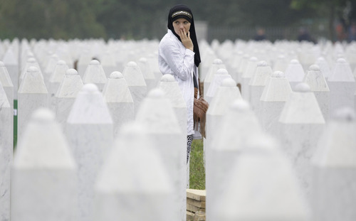 Bosnian woman Merima Nukic searches for her father's grave among gravestones during a funeral ceremony at the memorial center in Potocari, near Srebrenica, 160 kms east of Sarajevo, Bosnia, Thursday, July 11, 2013. People from around Bosnia and abroad have begun arriving in Srebrenica Thursday to commemorate 18th anniversary of the 1995 massacre and rebury recently identified victims exhumed from mass graves. The victims' bodies are still being exhumed from mass graves in the area, where Serbs had dumped them in an attempt to cover up the crime. Identified victims are buried each year on the massacre's anniversary at a memorial cemetery near Srebrenica. (AP Photo/Amel Emric)