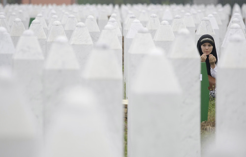 Bosnian woman Merima Nukic prays at the grave of her father during a funeral ceremony at the memorial center in Potocari, near Srebrenica, 160 kms east of Sarajevo, Bosnia, Thursday, July 11, 2013. People from around Bosnia and abroad have begun arriving in Srebrenica Thursday to commemorate 18th anniversary of the 1995 massacre and rebury recently identified victims exhumed from mass graves. The victims' bodies are still being exhumed from mass graves in the area, where Serbs had dumped them in an attempt to cover up the crime. Identified victims are buried each year on the massacre's anniversary at a memorial cemetery near Srebrenica. (AP Photo/Amel Emric)