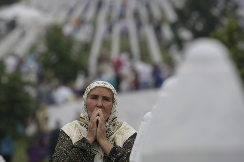 A Bosnian woman prays during a funeral ceremony at the memorial center in Potocari, near Srebrenica, 160 kms east of Sarajevo, Bosnia, Thursday, July 11, 2013. People from around Bosnia and abroad have begun arriving in Srebrenica Thursday to commemorate 18th anniversary of the 1995 massacre and rebury recently identified victims exhumed from mass graves. The victims' bodies are still being exhumed from mass graves in the area, where Serbs had dumped them in an attempt to cover up the crime. Identified victims are buried each year on the massacre's anniversary at a memorial cemetery near Srebrenica. (AP Photo/Amel Emric)