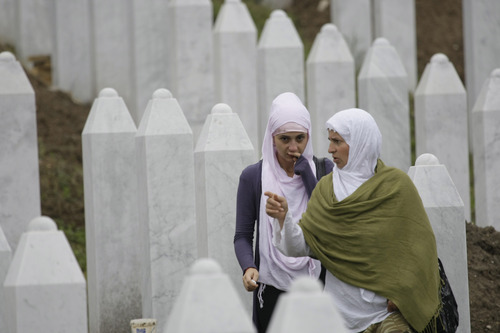 Bosnian women walk among the tombstones during a funeral ceremony at the memorial center in Potocari, near Srebrenica, 160 kms east of Sarajevo, Bosnia, Thursday, July 11, 2013. People from around Bosnia and abroad have begun arriving in Srebrenica Thursday to commemorate 18th anniversary of the 1995 massacre and rebury recently identified victims exhumed from mass graves. The victims' bodies are still being exhumed from mass graves in the area, where Serbs had dumped them in an attempt to cover up the crime. Identified victims are buried each year on the massacre's anniversary at a memorial cemetery near Srebrenica. (AP Photo/Amel Emric)