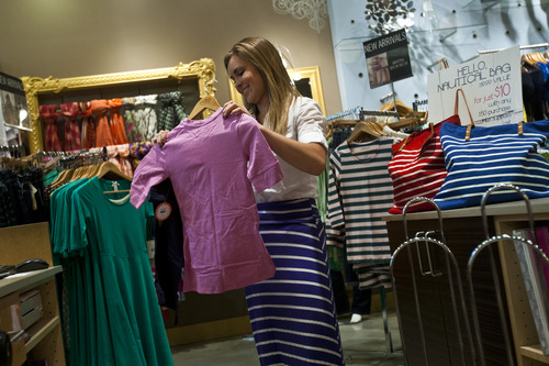 Chris Detrick     The Salt Lake Tribune At Salt Lake City-based DownEast, summer clothing is deeply discounted in July to make way for the new fall collections, which are being stocked in stores this month.  Here, shift leader Janie Matheson folds clothes at DownEast Basics in Fashion Place Mall on Wednesday July 10, 2013.