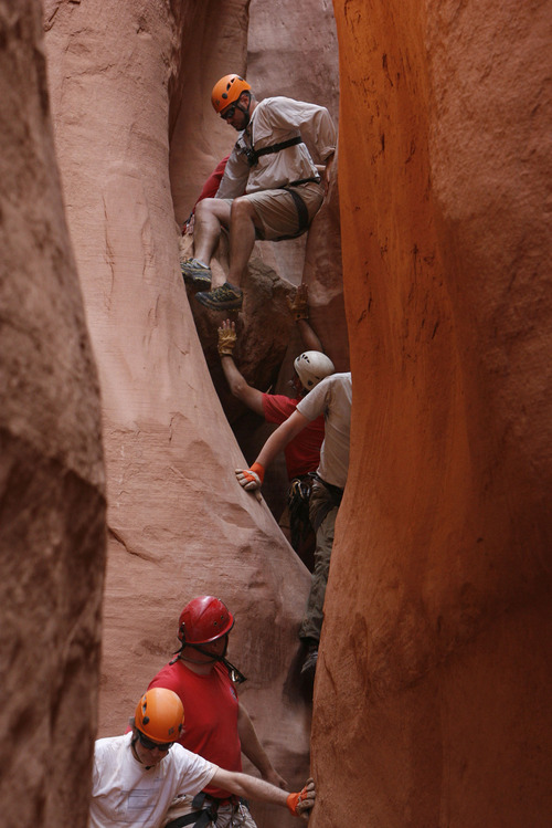 Francisco Kjolseth  |  The Salt Lake Tribune Using a number of techniques, the group makes its way down a slot canyon in Grand Staircase-Escalante National Monument, making sure to maintain a slow pace so no one gets hurt in such a cramped space.