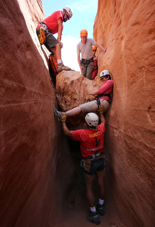 Francisco Kjolseth  |  The Salt Lake Tribune Nancy Green gets a helping hand from guide Rick Green as she bridges the gap during a descent down a slot canyon in southern Utah.